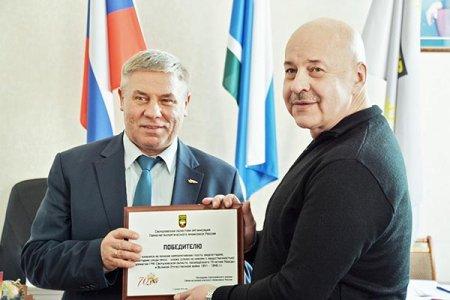 Валерий Кусков (слева) вручает награду корреспонденту газеты «Высокогорский горняк» Александру Кузьменкову.