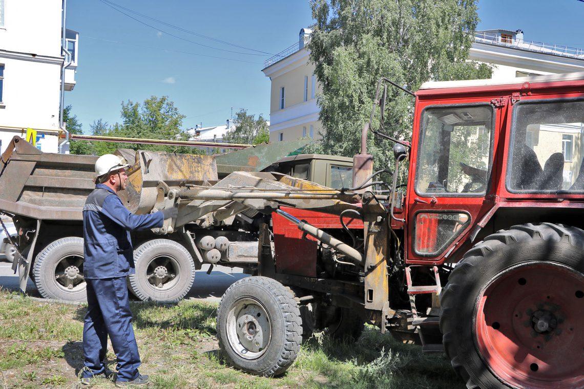 Алексей Ходневич командует погрузкой мусора.
